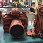 Ceramics I-  Dipping the Themed Coil Pieces in Iron Oxide